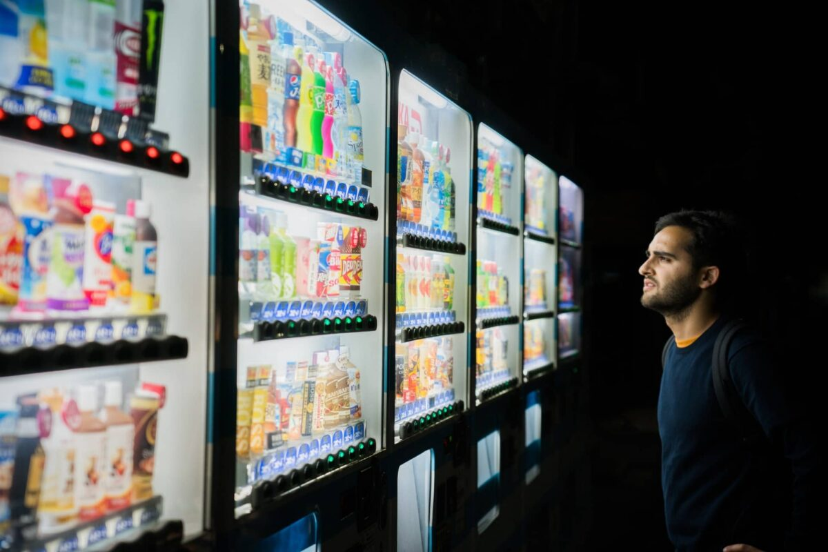 A person standing in front of a vending machine, overwhelmed by a huge variety of options.
