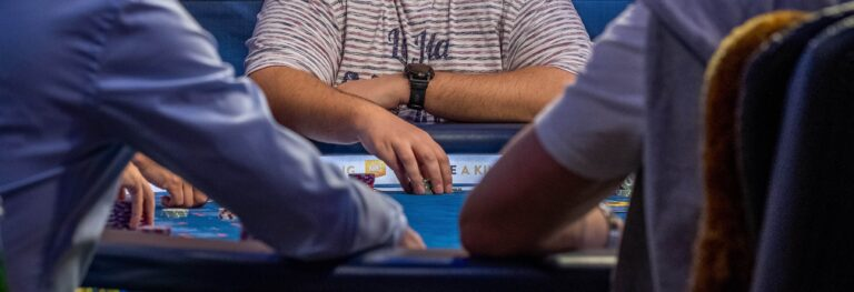A poker player making a bet at a poker table.